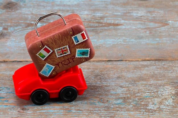 Carro de brinquedo vermelho com malas em um de madeira.
