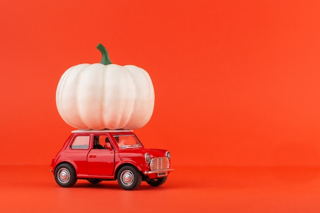 Carro de brinquedo vermelho com uma abóbora isolada