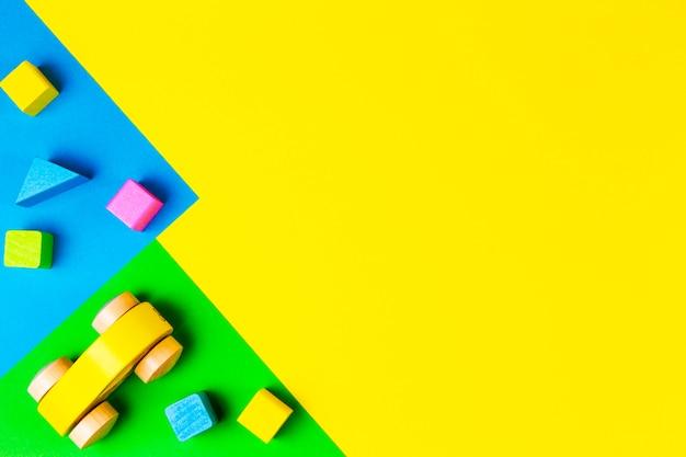 Carro de brinquedo vermelho de madeira com blocos coloridos em fundo geométrico verde azul amarelo. vista do topo
