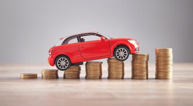 Carro de brinquedo vermelho e moedas na mesa.