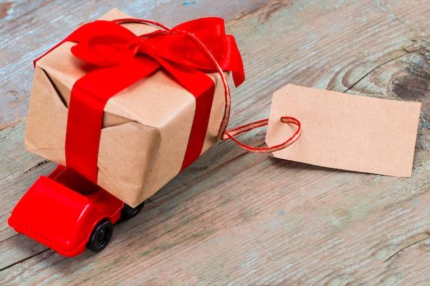 Carro de brinquedo vermelho entregando caixa de presentes com tag com espaço vazio para um texto em fundo de madeira.