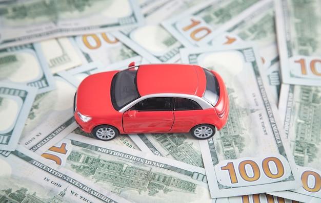 Carro de brinquedo vermelho nas notas de dólar.