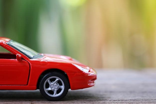 Carro de brinquedo vermelho no chão de madeira.