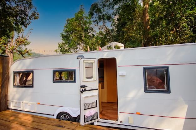 Carro de camping em um acampamento gramado sob um belo pôr do sol