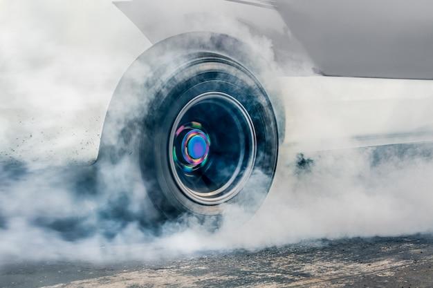 Carro de corrida de arrancada queima borracha dos pneus em preparação para a corrida
