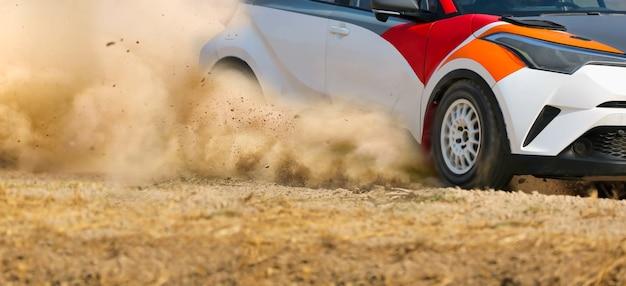 Carro de corrida de rali à deriva em curva em pista de terra.