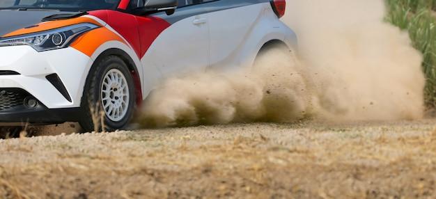 Carro de corrida de rali à deriva em pista de terra.