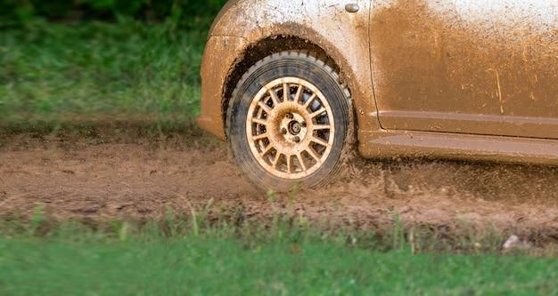 Carro de corrida de rali em pista lamacenta.