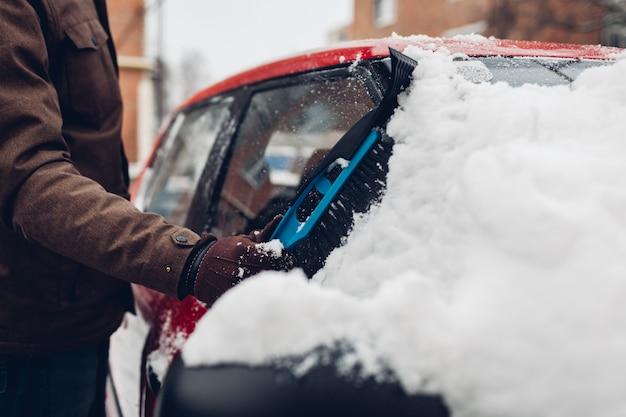 Carro de limpeza da neve usando vassoura. homem cuidando da janela do automóvel, removendo o gelo com escova ao ar livre