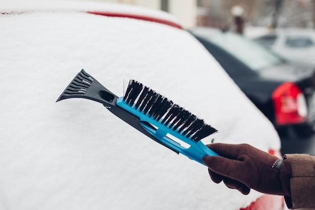 Carro de limpeza da neve usando vassoura. homem cuidando de automóvel remover gelo com escova ao ar livre