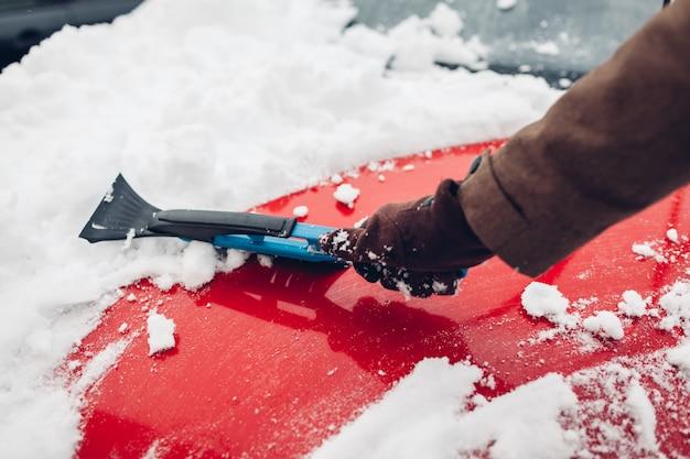 Carro de limpeza da neve usando vassoura. homem cuidando de pára-choques automóvel remover gelo com escova ao ar livre
