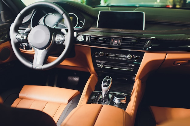 Carro de luxo moderno dentro. interior de carro moderno de prestígio. confortáveis assentos de couro marrom. cockpit de couro perfurado laranja.