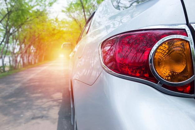 Carro de luz traseira na estrada verde