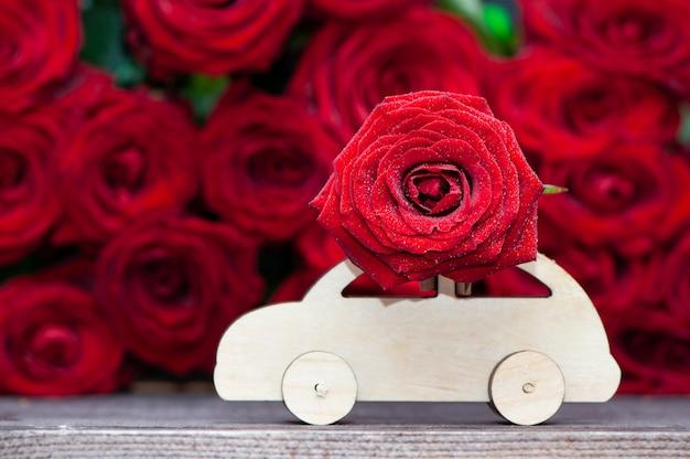 Carro de madeira transporta uma flor no fundo de rosas vermelhas.
