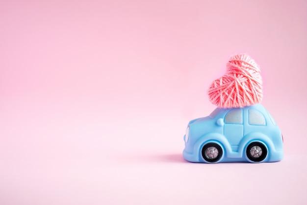 Carro de miniatura brinquedo azul entregando o coração de fio-de-rosa