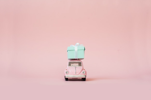Carro de modelo retrô de brinquedo rosa entregando a caixa de presente em fundo rosa