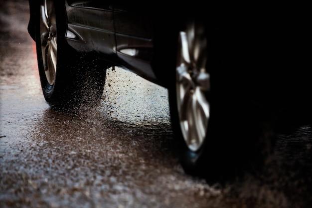 Carro de movimento na grande poça de chuva com água salpicando das rodas