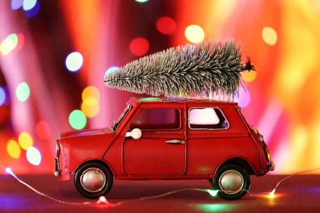 Carro de natal com árvore de natal. carro vermelho com uma árvore de natal decorativa