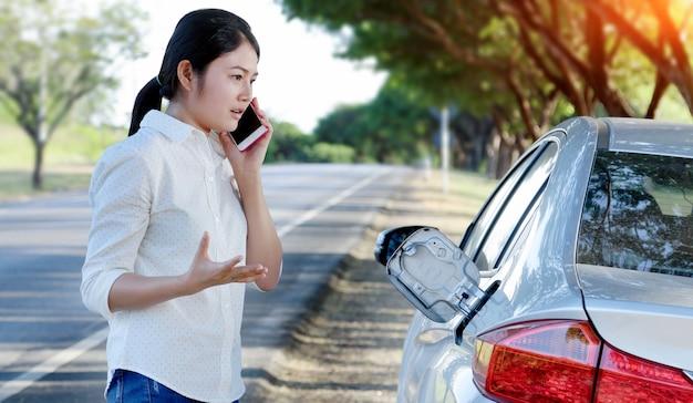 Carro de óleo para baixo e jovem mulher tentando pedir ajuda no telefone