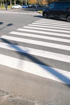Carro de passageiros na cidade na faixa de pedestres em um dia ensolarado de outono