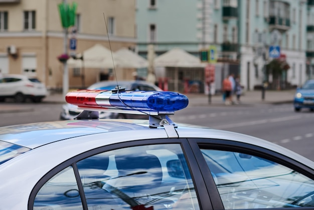Carro de polícia lightbar closeup contra rua da cidade