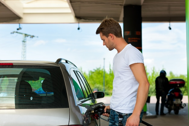 Carro de reabastecimento do homem no posto de gasolina