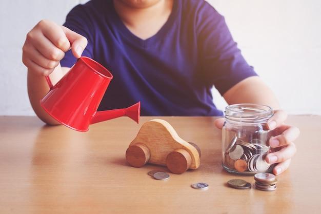 Carro de rega de menino e moedas. planejar o conceito de carro