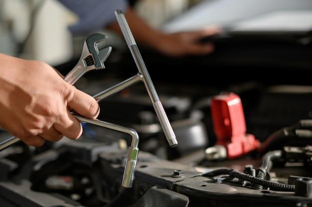 Carro de serviço de reparo mecânico de carro trabalhando no mecânico de garagem