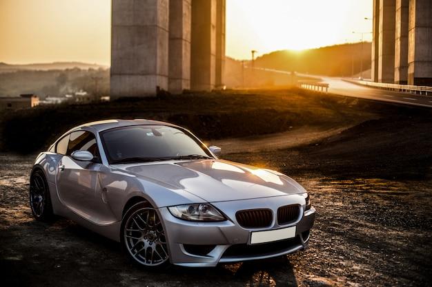 Carro desportivo de cor metálica cinza por do sol.