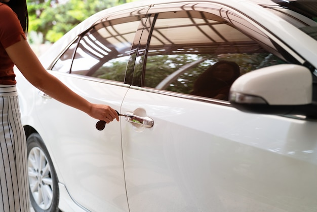 Carro destranca, mulher usa chave para abrir a porta do carro