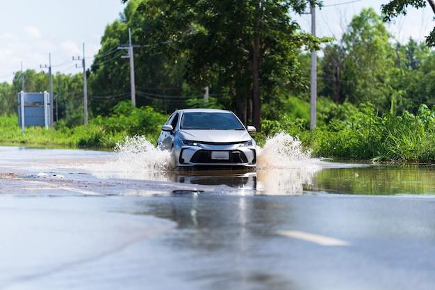 Carro dirigindo água de inundação, parte da área inundada na tailândia