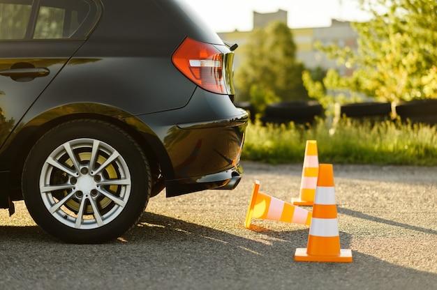 Carro e cones de trânsito laranja, lição de conceito de escola de condução, ninguém. tema de ensino a dirigir veículo. educação para carteira de habilitação