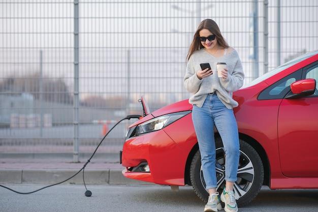 Carro elétrico cobrando na rua. carro ecológico conectado e baterias de carregamento. garota use café enquanto usa o smartphone e aguarda a fonte de alimentação conecte-se a veículos elétricos para carregar
