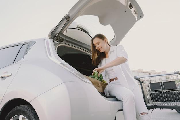 Carro elétrico de carregamento de mulher no posto de gasolina elétrico
