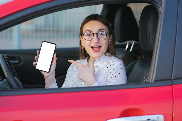 Carro elétrico de carregamento e olhando para o aplicativo no celular. feche a tela do smartphone. mão segurando o dispositivo inteligente com visor branco. aplicativo móvel para transporte ecológico