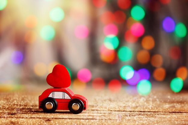 Carro em miniatura, carregando um coração vermelho no telhado. amor de conceito de férias