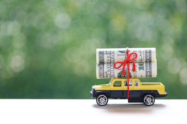 Carro em miniatura e notas no fundo verde da natureza, economizando dinheiro para o carro, finanças e empréstimo de carro, investimento e conceito de negócios
