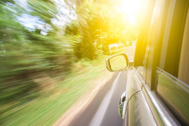 Carro em movimento na estrada entre a floresta