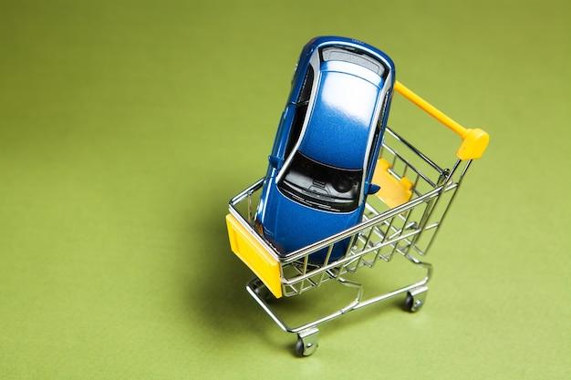 Carro em um carrinho sobre um fundo verde. comprando um carro
