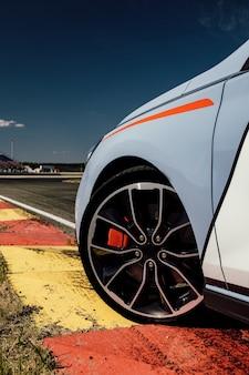 Carro esporte na pista. a bela roda de um carro esporte, com o asfalto, em uma pista de corrida.