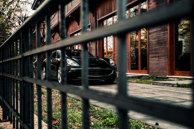 Carro esporte sedan, cor preta em pé na frente de um edifício, vista frontal através de um daqui.