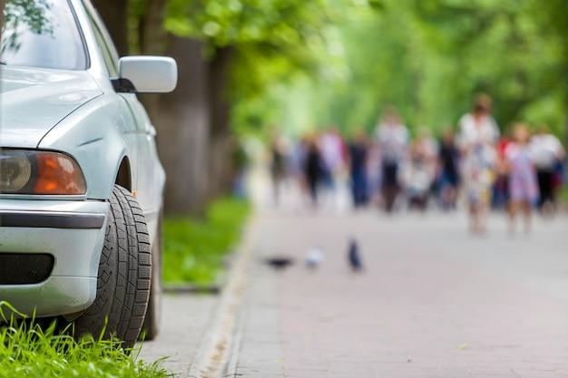 Carro estacionado na zona pedonal ao longo da rua com pessoas a andar num dia de verão.