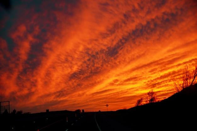 Carro ilumina a estrada neste pôr do sol crepuscular cênica