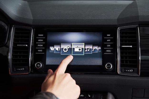 Carro inteligente e internet das coisas muito conceito. o dedo aponta para o console do carro e os ícones aparecem fora da tela