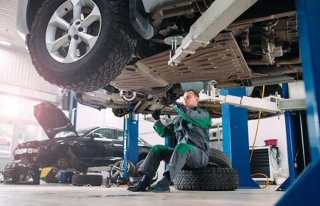Carro levantado em serviço automotivo para conserto, trabalhador conserta a roda