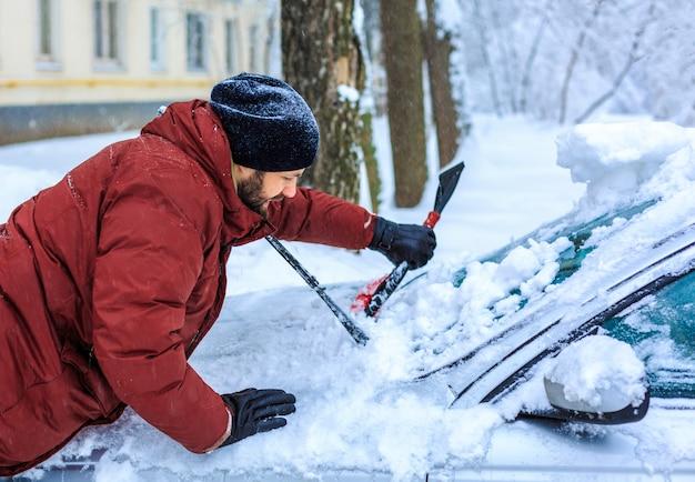 Carro limpo jovem após tempestade de neve com raspador