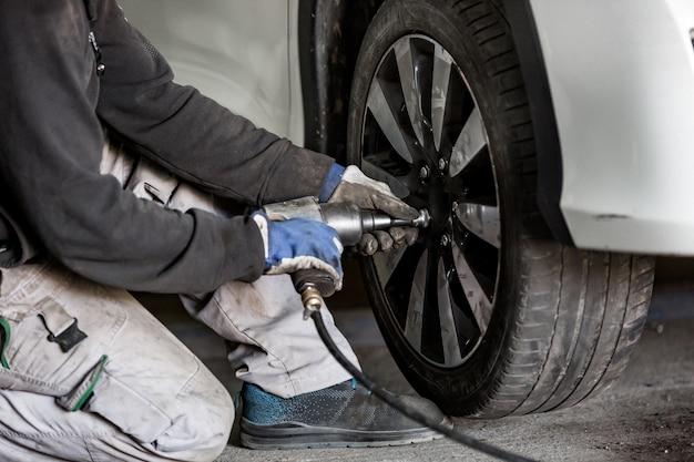 Carro, mecânico de automóveis trocando pneus, rodas do carro por chave pneumática, centro de serviço