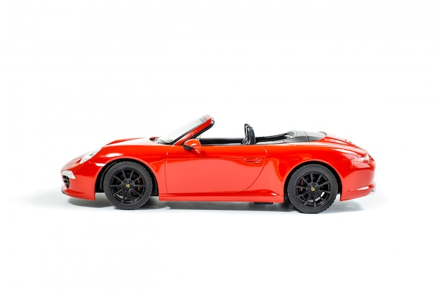 Carro modelo vermelho do brinquedo isolado no fundo branco. vista lateral. foco suave.