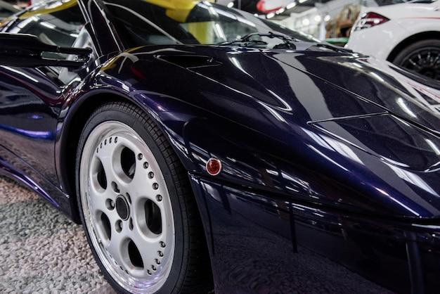 Carro moderno azul perfeitamente polido estacionado dentro da exposição