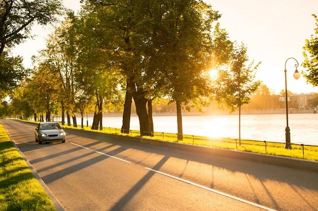 Carro moderno, dirigindo ou viajando na estrada de asfalto no parque ao pôr do sol, luz da rua e rio no fundo